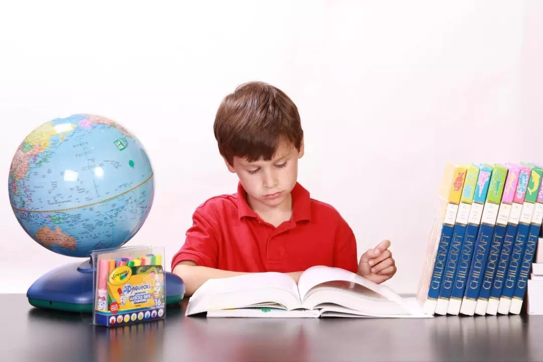 boy is read across america at the table with a globe, extra books, and crayons on to of it.